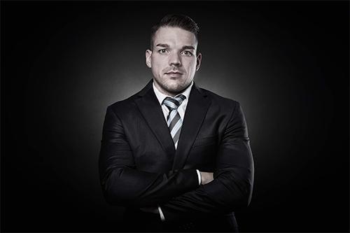 jetzt-scheiden-lassen-de-Rechtsanwalt Manuel Tripp im Anzug vor dunklem Hintergrund